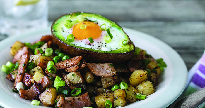 Avocado baked eggs with turkey bacon parsnips and peas